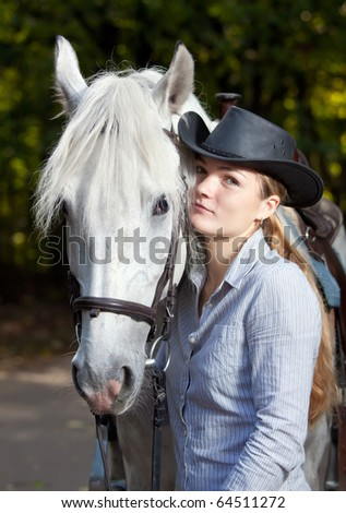 Young Lady in hat hugging her horse