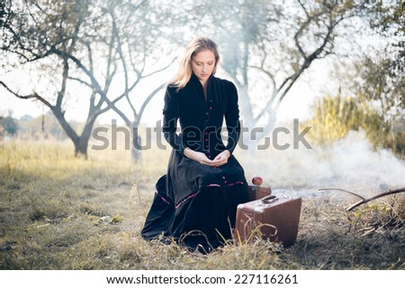 Young lady in retro overcoat with vintage suitcase waiting in autumn park with burning leaves and smoke copy space background - stock photo
