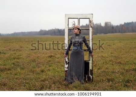 Young lady in retro style dress stands alone back to the old scratched door in the autumn field - romantic loneliness concept