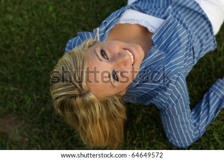 young lady in the grass looking up at camera - stock photo