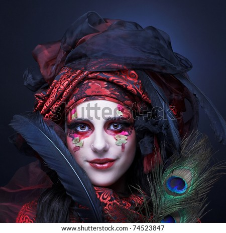 Young lady in turkish style in black and red silk and with feathers - stock photo