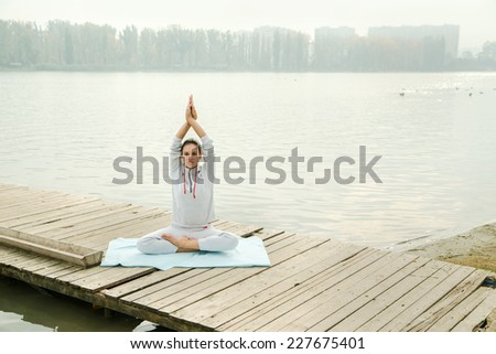 Young lady is doing yoga exercise outdoor in the city park - stock photo