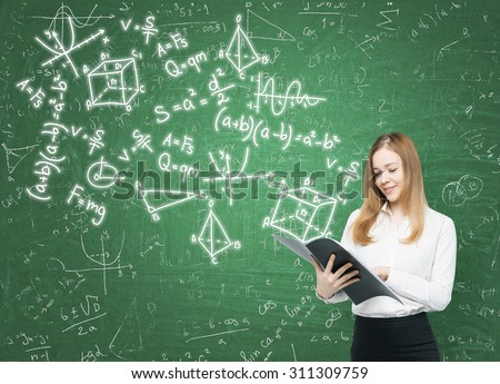 Young lady is holding a black document folder and a range of math formulas are drawn on the green chalkboard. - stock photo