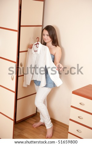 Young lady is trying on white shirt near wardrobe