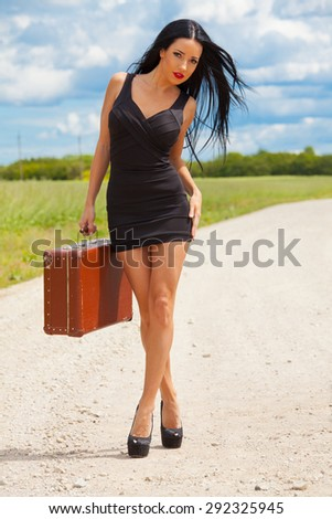 young lady is waiting car on village road - stock photo