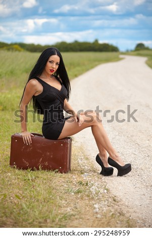 young lady is waiting car on village road