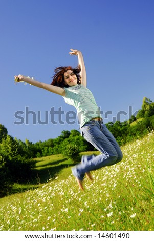 Young lady jumping in a field of wild flowers - stock photo