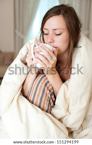 Young lady just woke up sitting in bed checking her laptop computer and having a cup of coffee.