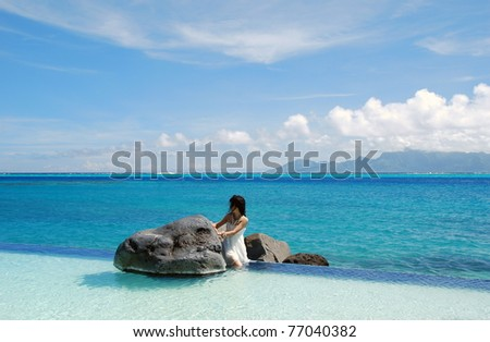 Young lady like a little mermaid , sitting alone between the rocks  in the swimming pool with  scene of Moorea island on the background . - stock photo