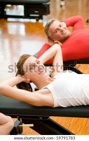 Young lady making sit-ups on bench at gym - stock photo