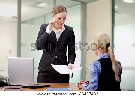 Young Lady Manager in glasses disappointed of her worker - stock photo