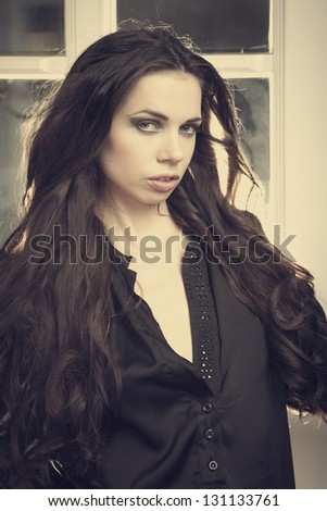 Young lady model posing for fashion and glamour photos on indoor location of hotel corridors