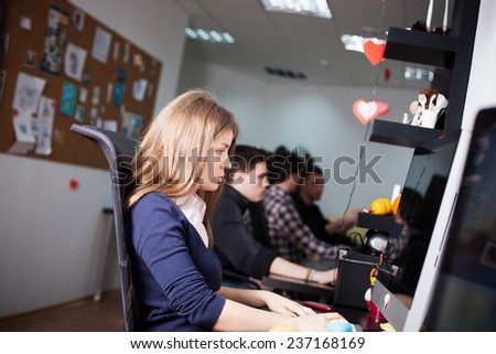 Young lady - office worker sitting at workplace next to the computer. Office of young specialists - designers. - stock photo