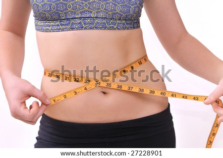 young lady on a diet measuring her waist line