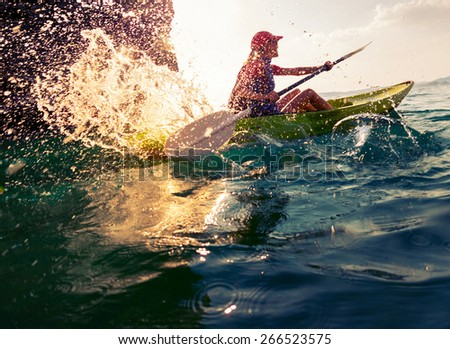 Young lady paddling hard the sea kayak with lots of splashes - stock photo