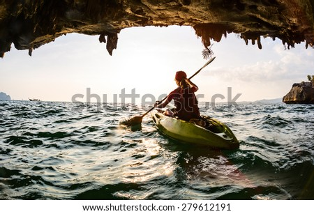Young lady paddling the kayak in a sea near the cave exit - stock photo