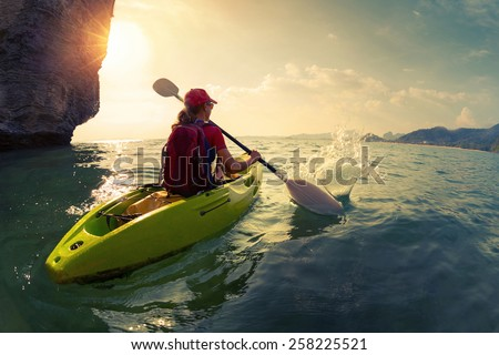 Young lady paddling the kayak near the cliff at sunset - stock photo