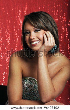 Young lady posed on red background in evening dress