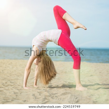 Young lady practicing yoga. Beautiful woman posing at the summer sand beach. Workout at sea coast. Beautiful fit tan girl. Fitness model caucasian ethnicity outdoors. Weight loss exercise. Meditation. - stock photo