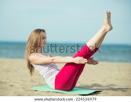 Young lady practicing yoga. Beautiful woman posing at the summer sand beach. Workout near ocean sea coast. Beautiful fit tan girl. Fitness model outdoors. Weight loss exercise. Meditation. - stock photo