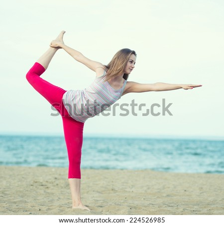 Young lady practicing yoga. Beautiful woman posing at the summer sand beach. Workout near ocean sea coast. Fitness model caucasian ethnicity outdoors. Weight loss exercise. Meditation. - stock photo