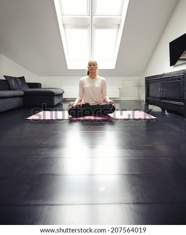 Young lady practicing yoga in her living room. Fit woman sitting on floor meditating in lotus position at home. - stock photo