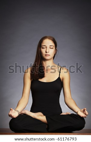 Young lady practicing yoga in lotus posture (Padmasana) with eyes closed. - stock photo