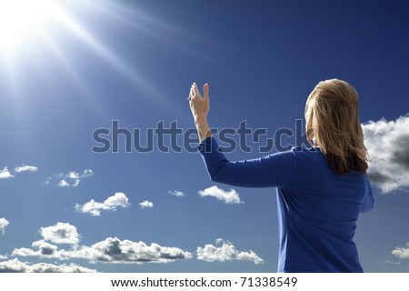 Young lady raising her arms in worship and praise while facing the rising sun. - stock photo