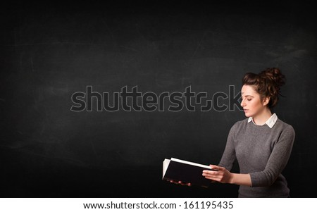 Young lady reading a book in front of a blackboard  - stock photo