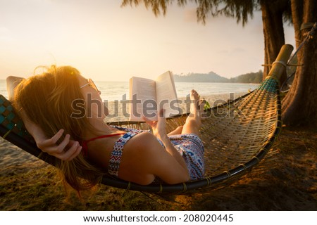 Young lady reading a book in hammock on a beach at sunset - stock photo