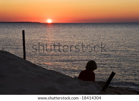 Young lady relaxing by the shore as the sun sets. - stock photo