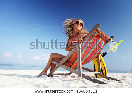 Young lady relaxing in a chair on a tropical beach with white sand - stock photo