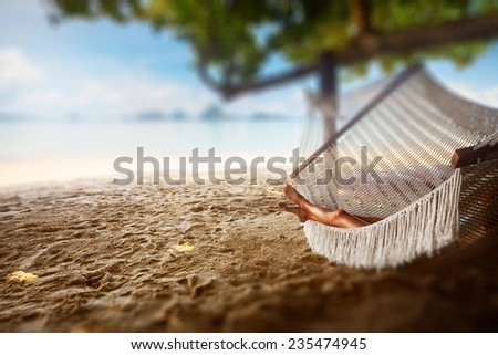 Young lady relaxing in the hammock on the sandy beach with view on remote tropical islands - stock photo