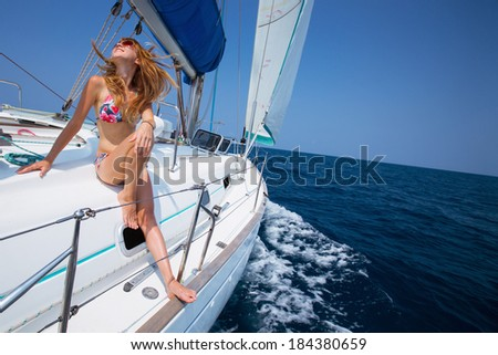 Young lady relaxing on the deck of the sail boat in the tropical sea at sunny day - stock photo
