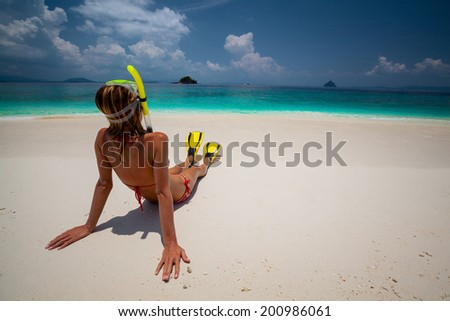 Young lady relaxing on the tropical sandy beach with snorkeling gear - stock photo