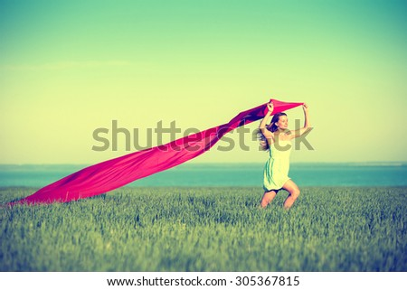 Young lady runing with tissue in green field. Beautiful happy woman walking in the summer rural meadow. Beautiful fit tan girl. Sexy slim model caucasian ethnicity outdoors. - stock photo