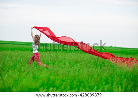 Young lady runing with tissue in green field. Beautiful happy woman walking  in the summer rural meadow. Outdoor summer portrait of pretty sport style woman jumping with fabric. Beautiful fit tan girl - stock photo
