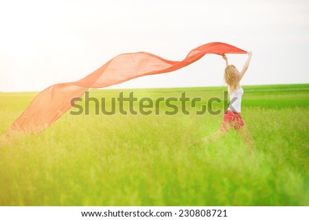 Young lady runing with tissue in green field.  Outdoor summer portrait of pretty sport style woman jumping with fabric. Beautiful fit tan girl. Sexy slim model caucasian ethnicity outdoors. - stock photo