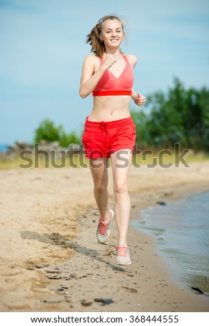 Young lady running at the sunny summer sand beach. Workout.  Jog - stock photo