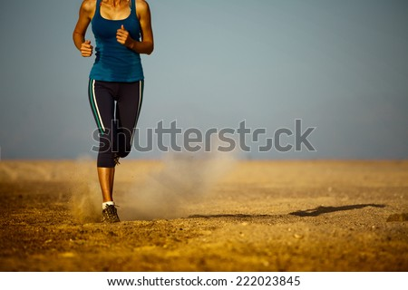 Young lady running in the desert - stock photo