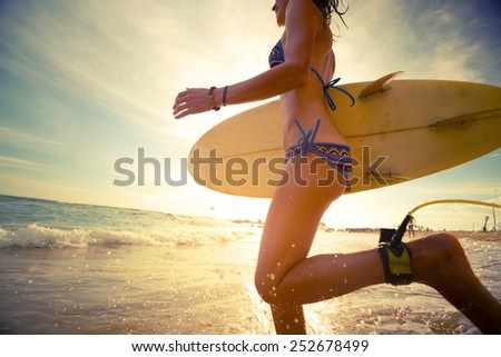 Young lady running into the sea with surf board at sunset - stock photo