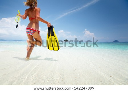 Young lady running into tropical blue sea with snorkeling gear at sunny day