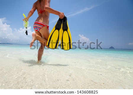 Young lady running into tropical blue sea with snorkeling gear at sunny day - stock photo