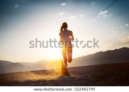 Young lady running on the desert at sunset - stock photo