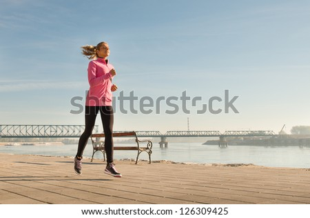 young lady running outside on sunny day - stock photo