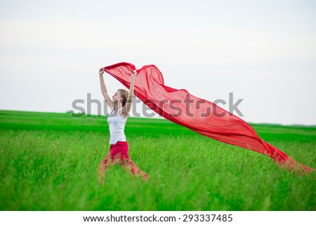 Young lady running with tissue in green field. Beautiful happy woman walking  in the summer rural meadow. Outdoor summer portrait of pretty sport style woman jumping with fabric. Beautiful fit tan girl
