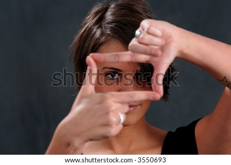 Young Lady, 20's. Hand on frame shape in front of eye.