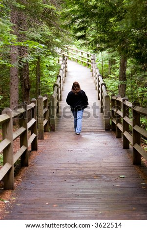 Young lady setting out on a walkway through the forest - stock photo