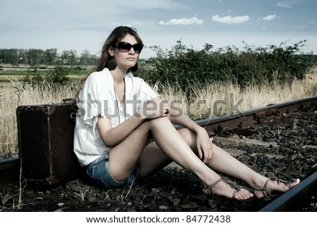 Young lady sit on the rails with old fashioned suitcase