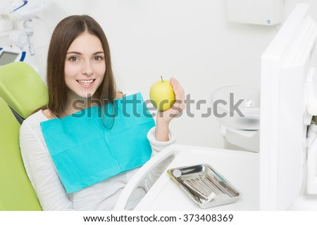 Young lady sitting in the dentist's chair and holding a green apple in her hand at dentist's office.